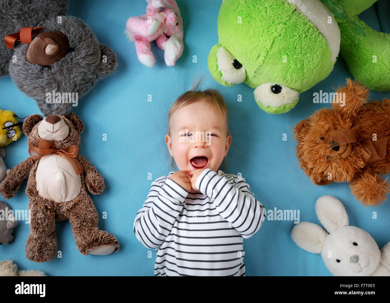 Happy one year old boy lying with many plush toys - Stock Image