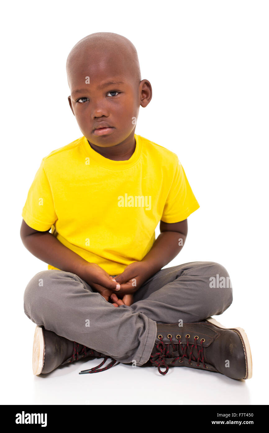 sad African American boy sitting on white background Stock Photo