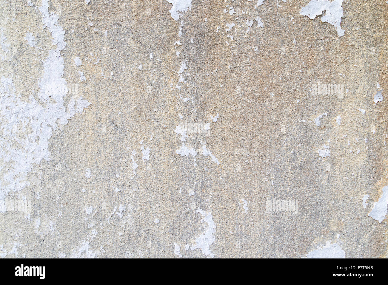 Weathered concrete wall with white plastering/paint peeled off. Stock Photo
