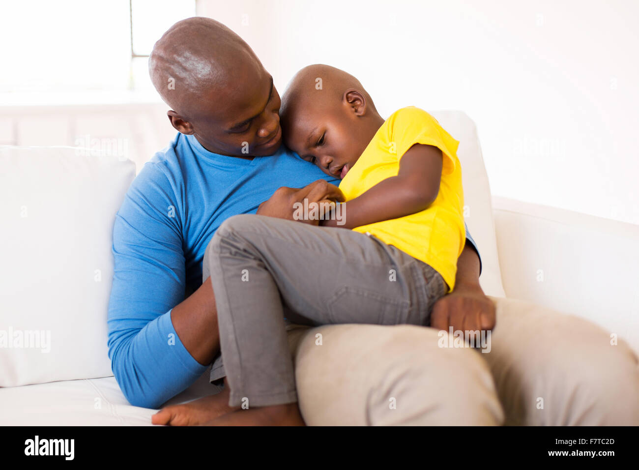 African American father comforting his ill son at home - Stock Image