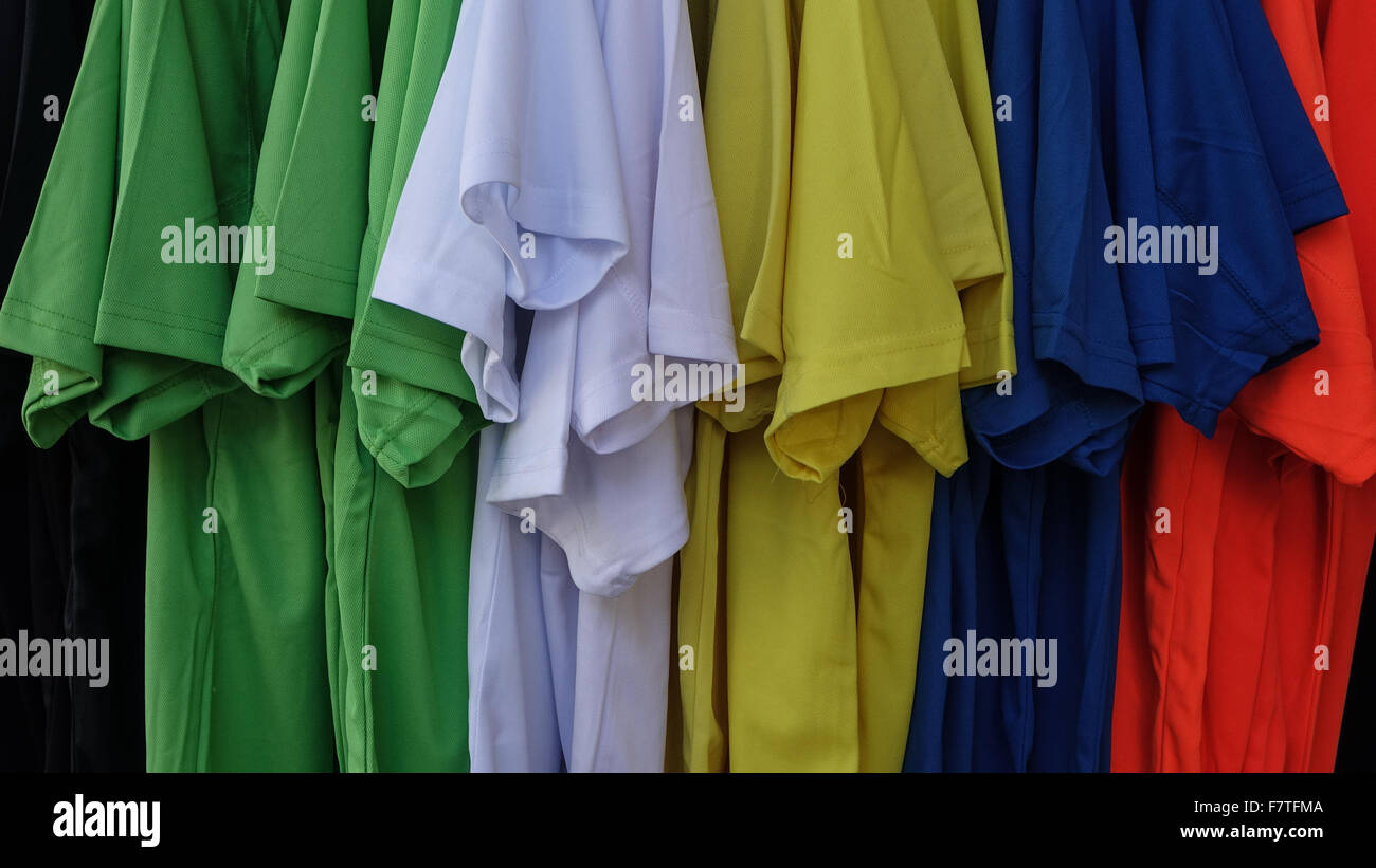 Rack of coloured Tee Shirts. Colored green white blue yellow red - Stock Image