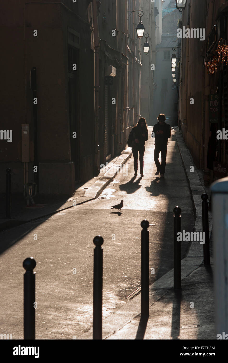 France, Paris, Young couple walking down a narrow street on the left bank - Stock Image