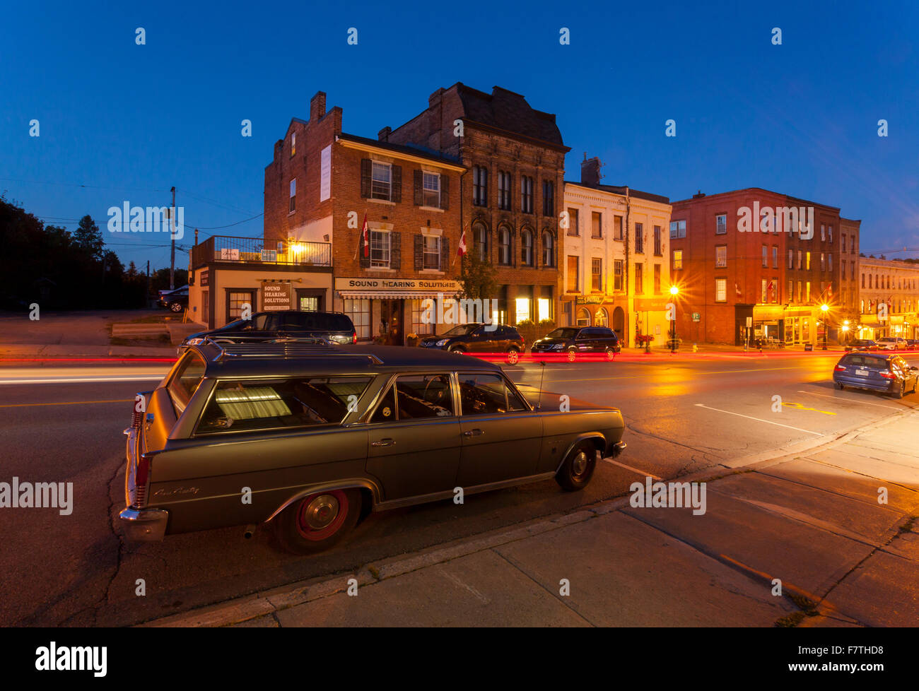 Walton Street with a Rambler Ambassador in the foreground in downtown Port Hope at dusk. Ontario, Canada. - Stock Image