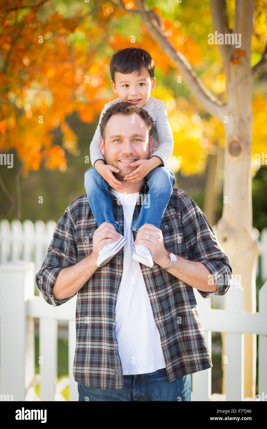 Happy Mixed Race Boy Riding Piggyback on Shoulders of Caucasian Father. - Stock Image