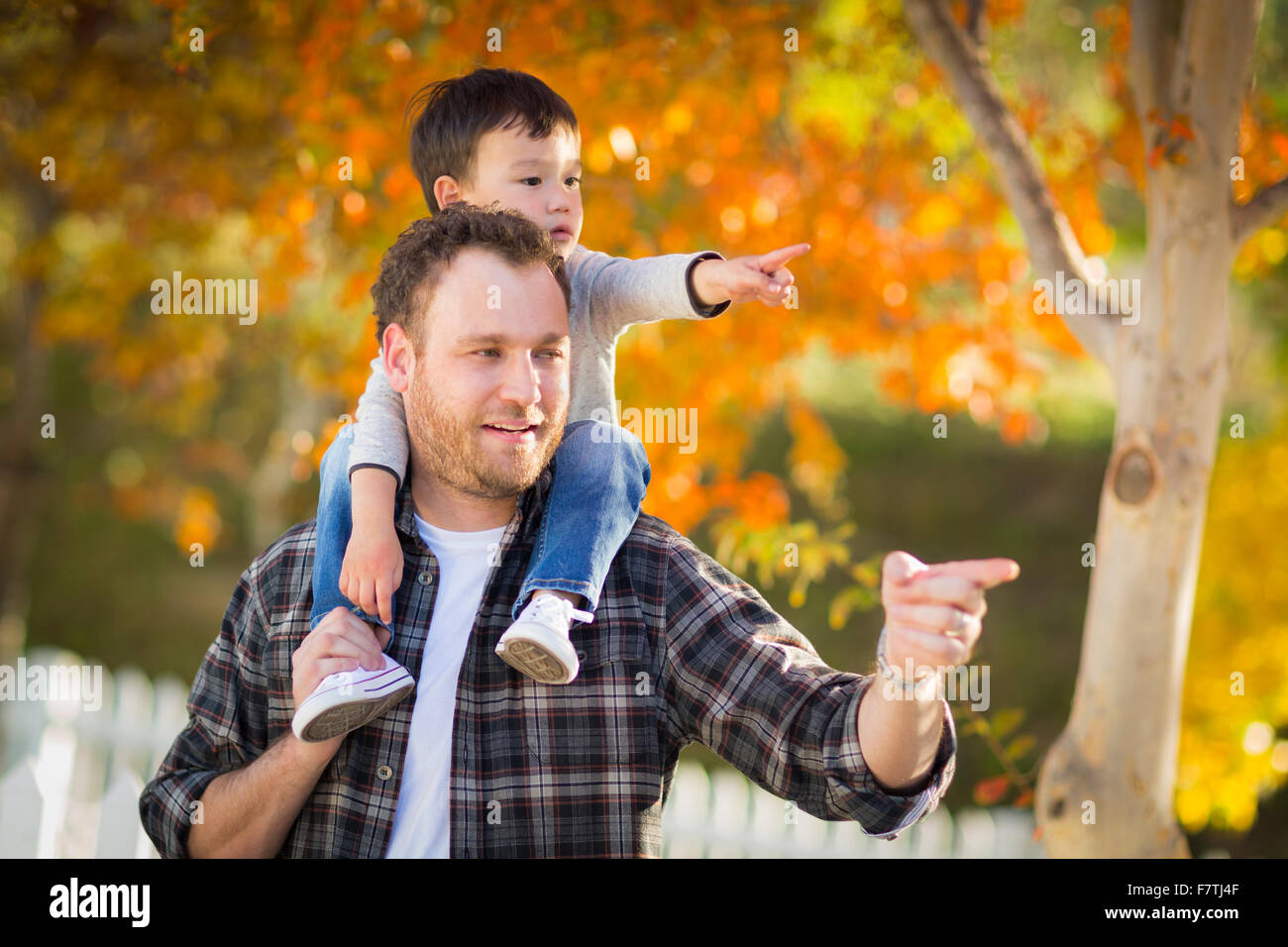 Happy Mixed Race Boy Riding Piggyback and Pointing on Shoulders of Caucasian Father. - Stock Image