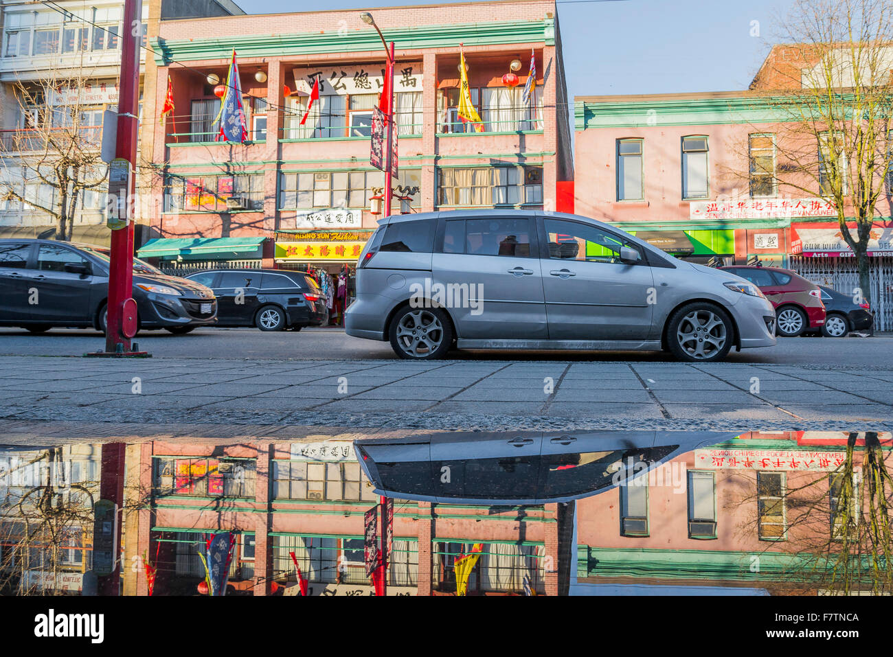 Reflections in puddle on Pender Street, Chinatown,  Vancouver, British Columbia, Canada - Stock Image
