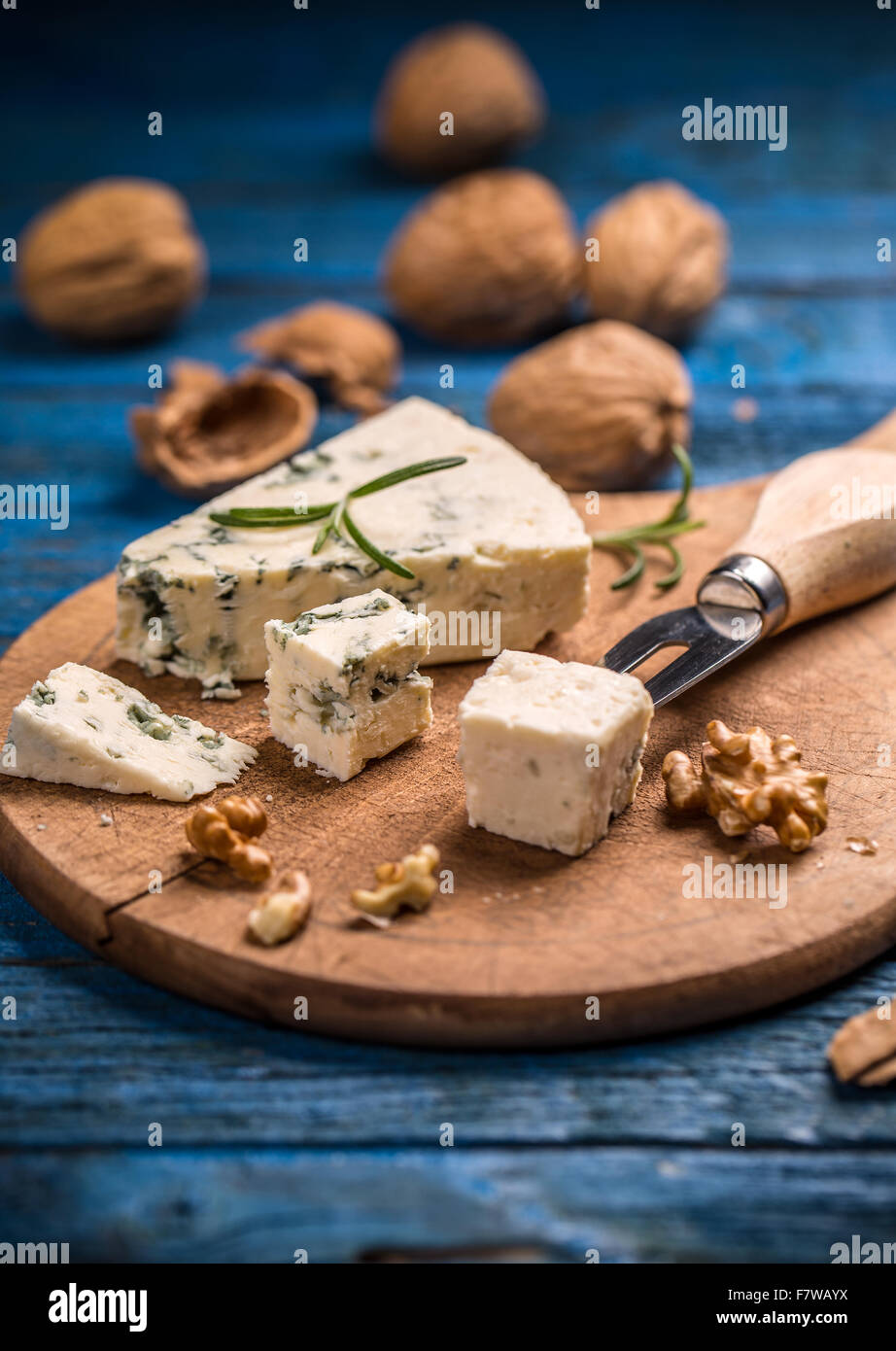 Blue cheese with nuts on cutting board - Stock Image