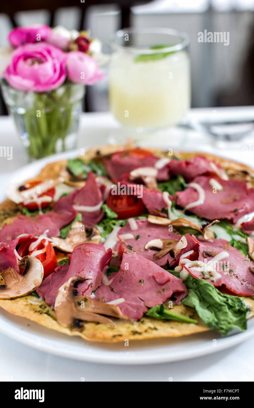 Pizza Topped with Meet and Vegetable on Plate - Stock Image