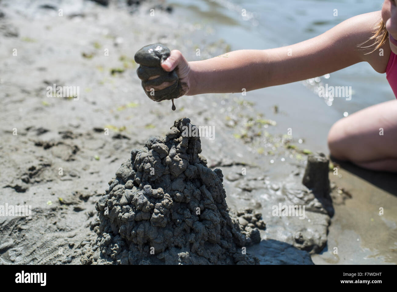 Preteen girl in swimming suit sitting in shallow water on river bank building sand castle - Stock Image