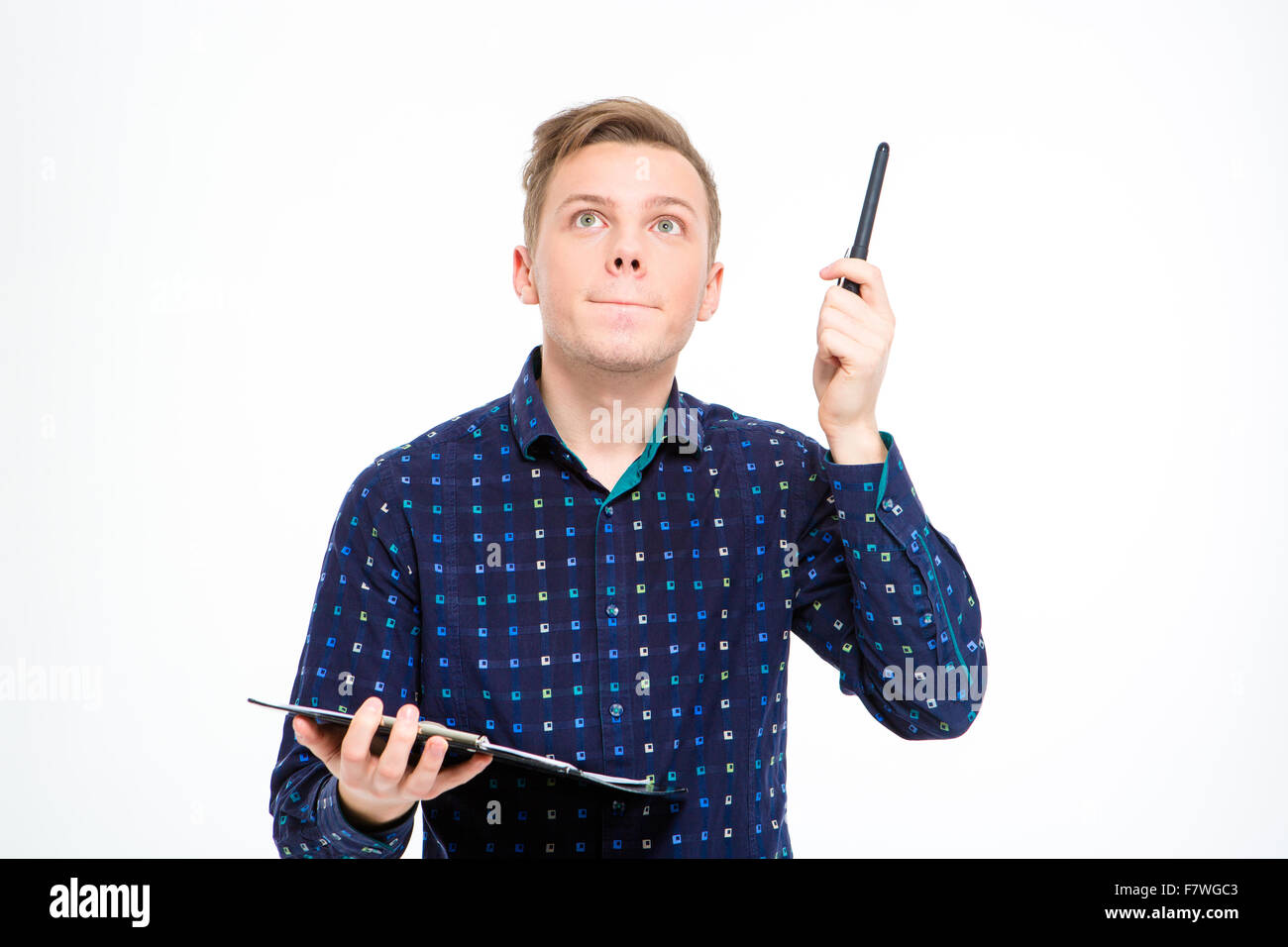 Concentrated handsome young man in checkered shirt holding clipboard and pointing up by pen over white background - Stock Image