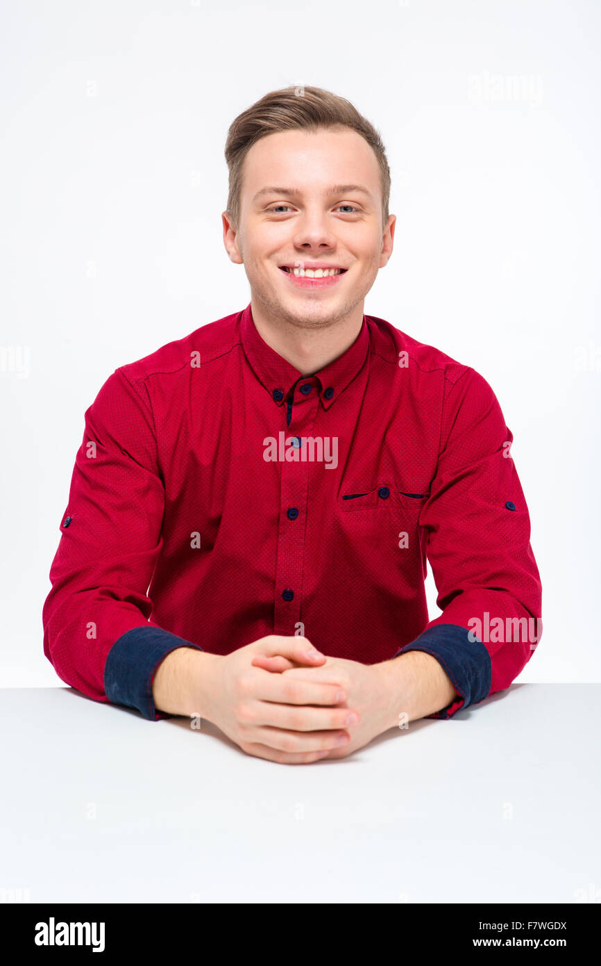 Positive cheerful young male in red shirt sitting and looking camera over white background - Stock Image