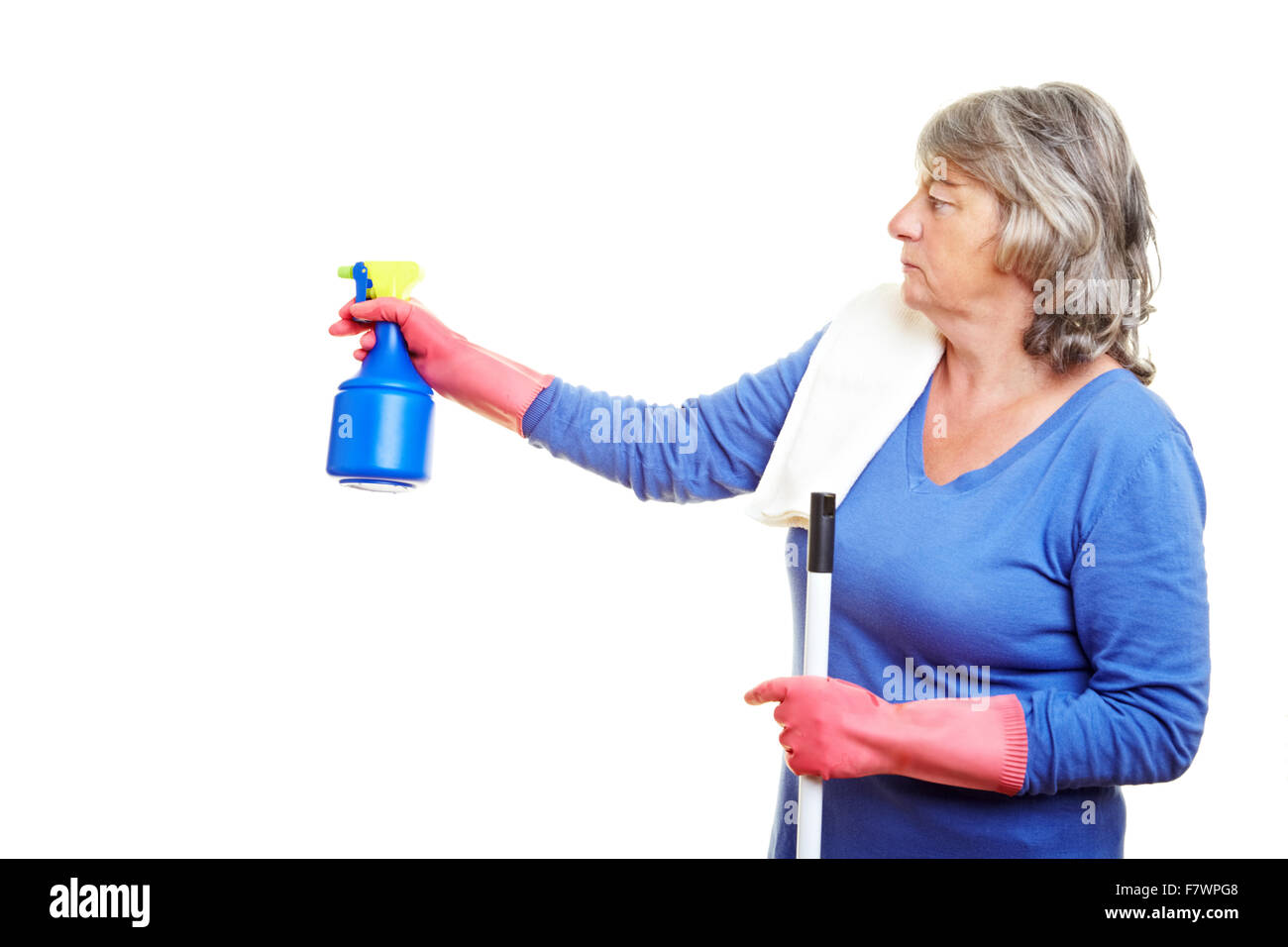 Elderly cleaning lady using a spray bottle - Stock Image