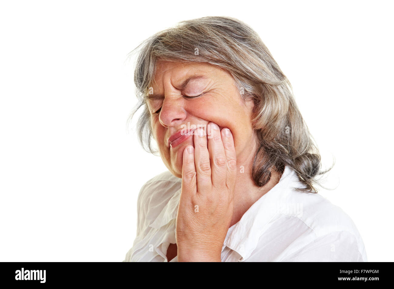Elderly woman with toothache holding her cheek - Stock Image