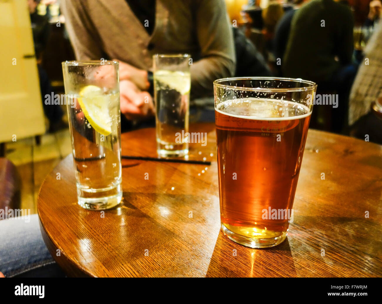 A pint of beer and 2 soft drinks on a pub table - Stock Image