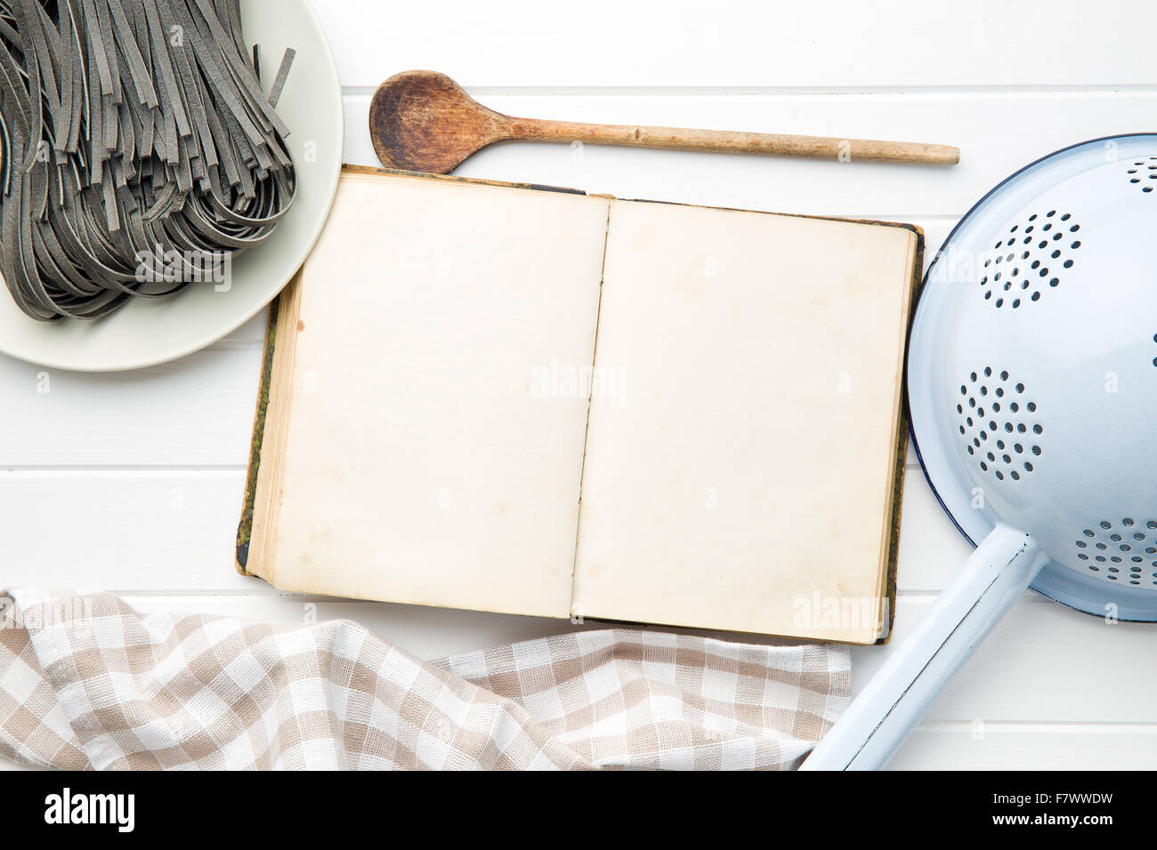 cookbook and black noodles with squid sepia ink on white table - Stock Image