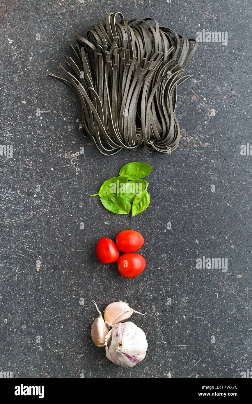 noodles, garlic, tomatoes and basil leaves on old kitchen table - Stock Image