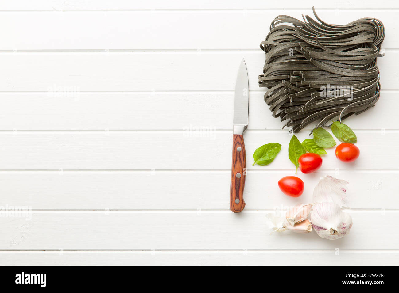 noodles, garlic, tomatoes and basil leaves on white table - Stock Image