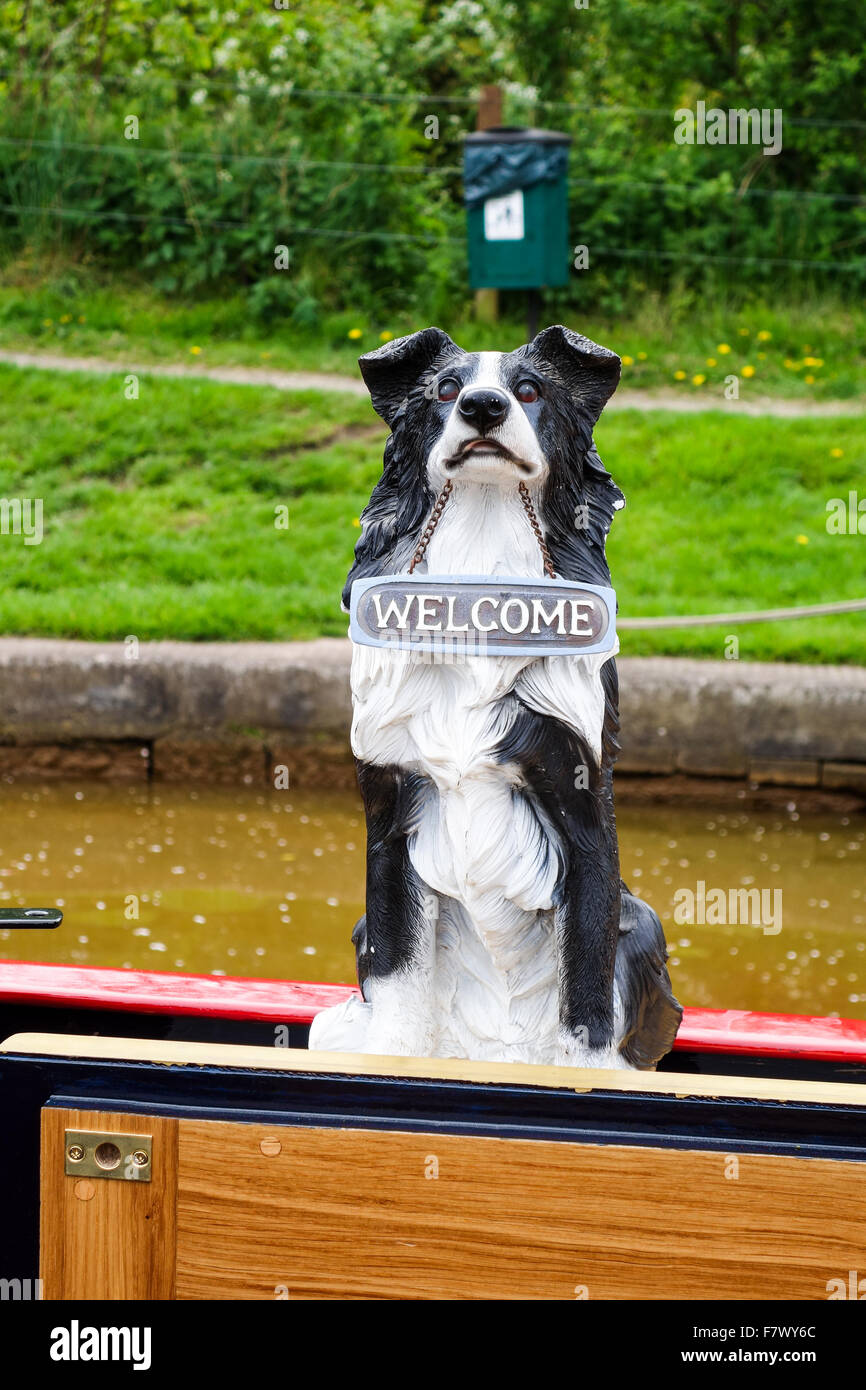 A plastic model of a Border Collie dog with a sign around it's neck saying 'welcome' on a narrow boat - Stock Image