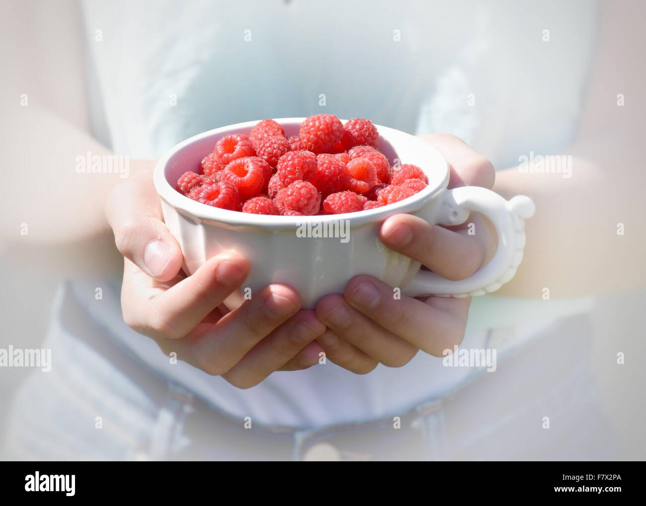 Close-up of girl holding raspberries in a cup - Stock Image