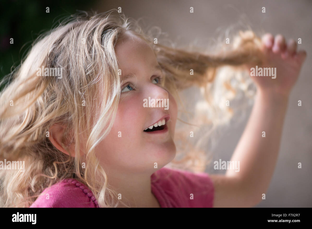 Girl twisting her hair - Stock Image