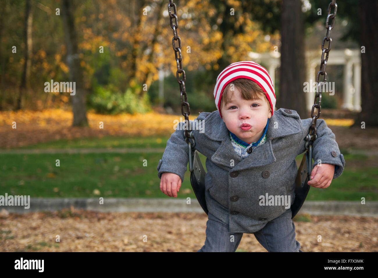 Boy on a swing puckering lips - Stock Image