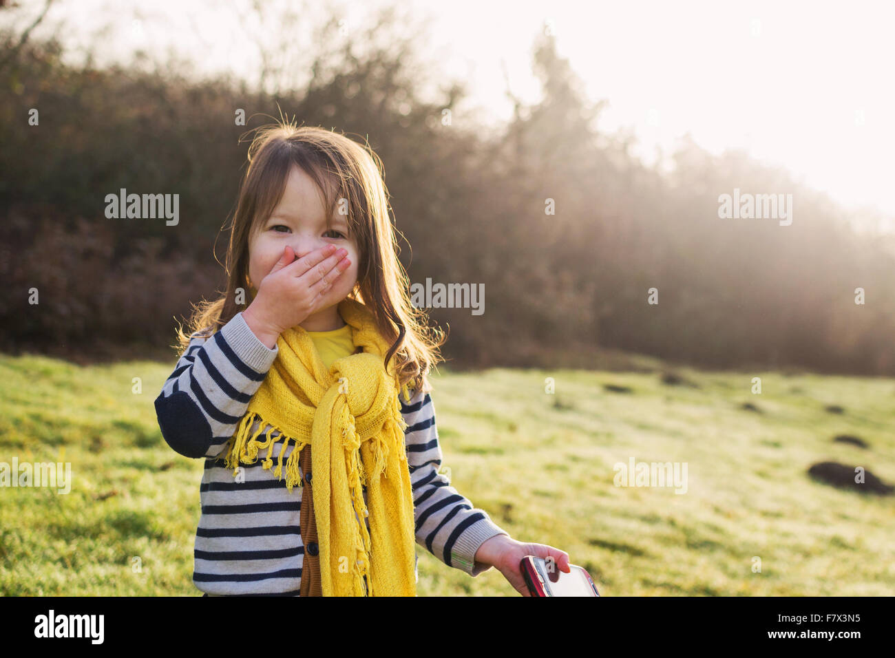 Laughing girl with hand in front of her mouth, holding mobile phone Stock Photo