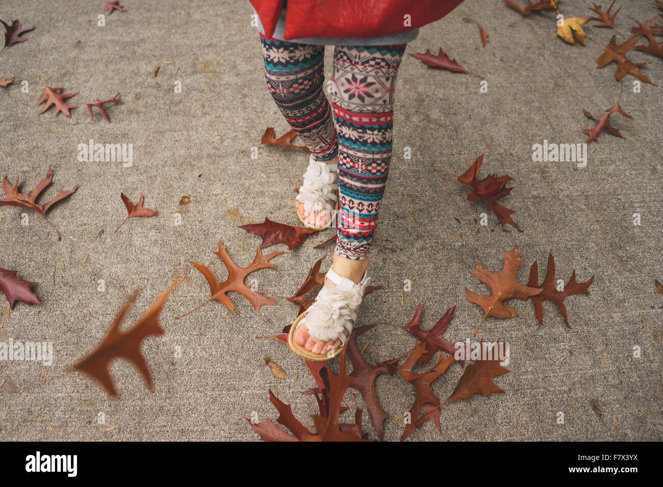 Girl skipping along a path in autumn - Stock Image