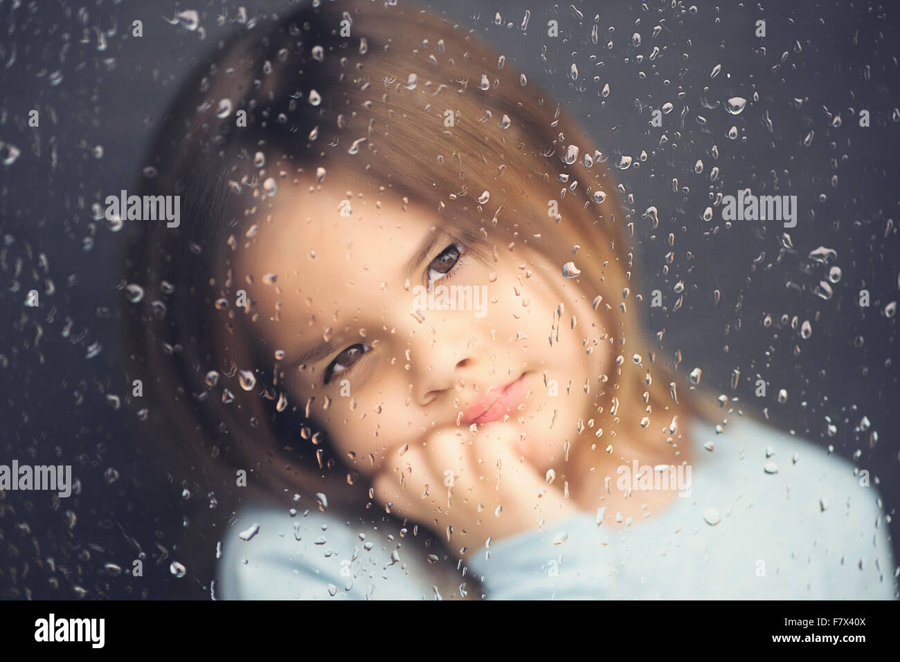 Girl looking out of a window on a rainy day Stock Photo