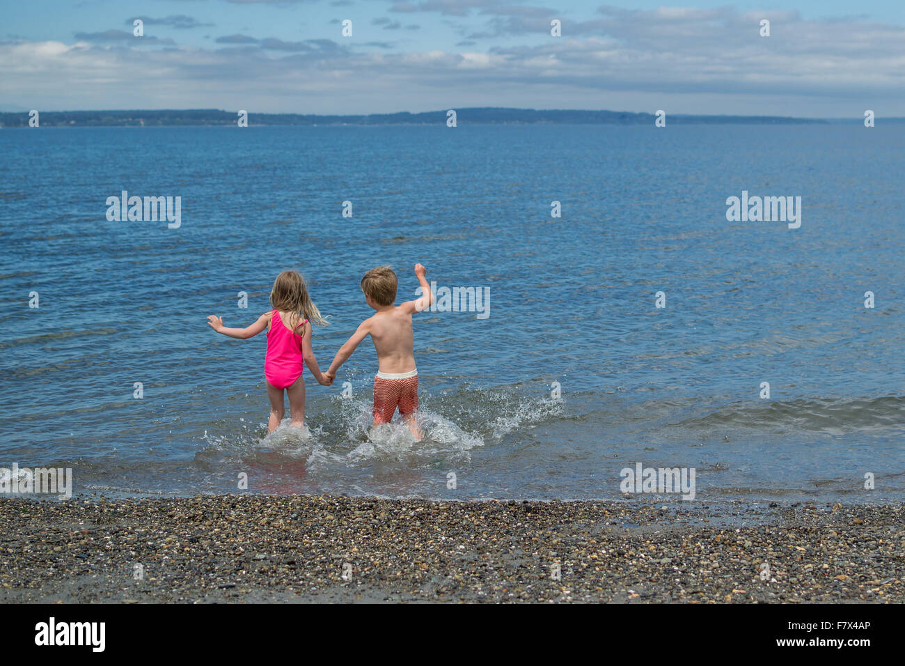 Boy and girl holding hands running into the sea Stock Photo