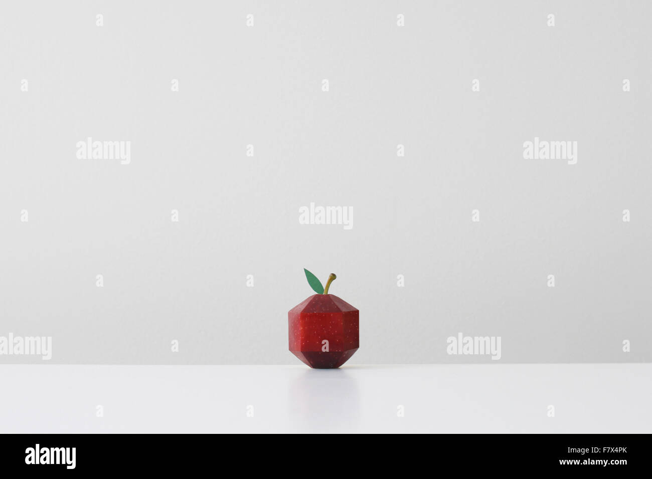 Red apple crafted into geometric shape imitating paper origami - Stock Image