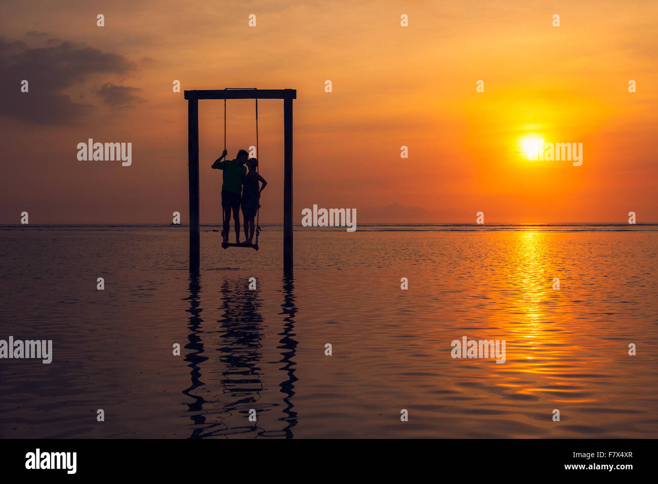Silhouette of Man and woman kissing, standing on a swing in sea at sunset, Indonesia Stock Photo