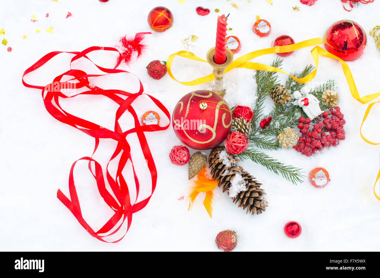 Christmas toys and jewelry on snow from candles Stock Photo