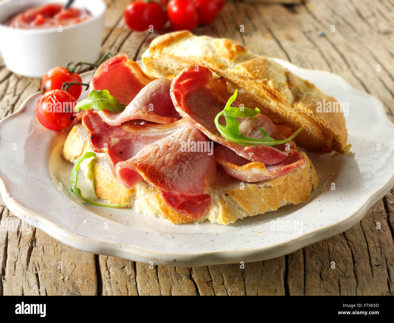 Prepared bacon toasted sandwich in white bread on a plate - Stock Image