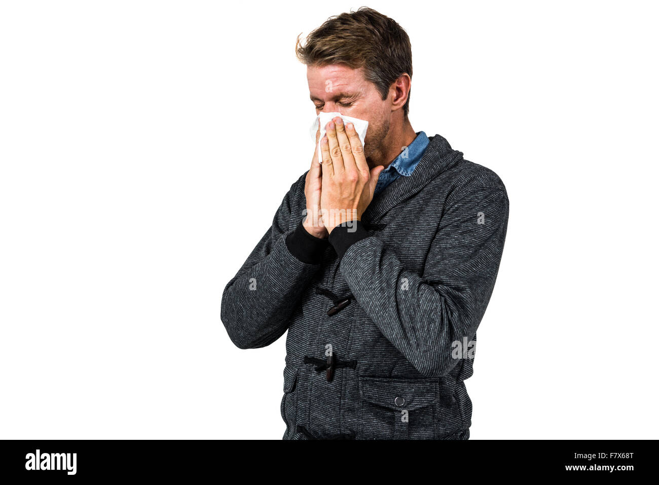Warmly dressed man blowing his nose - Stock Image