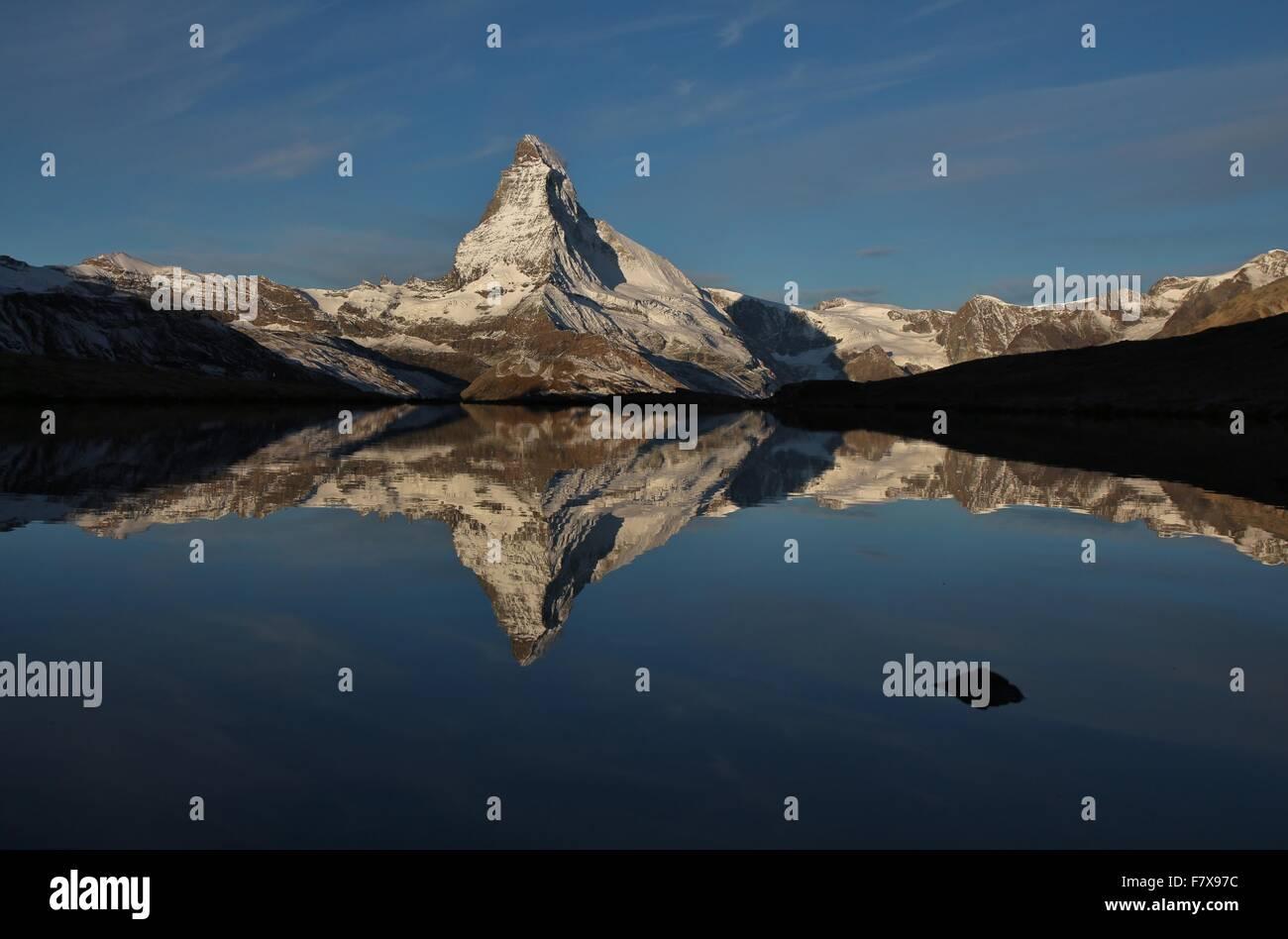 Snow capped Matterhorn mirroring in lake Stellisee - Stock Image