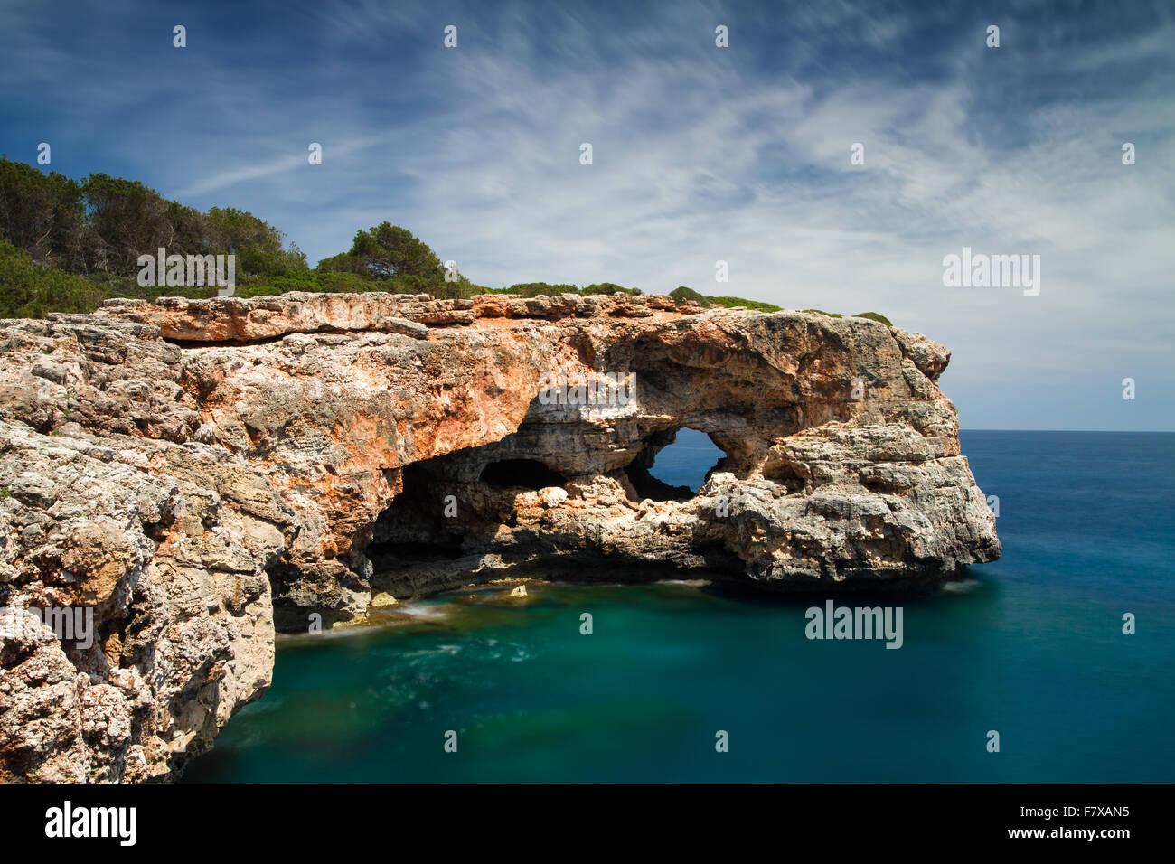 Hole in the rock at Cala Sa Nau - Long exposure version, Mallorca, Baleares, Spain - Stock Image
