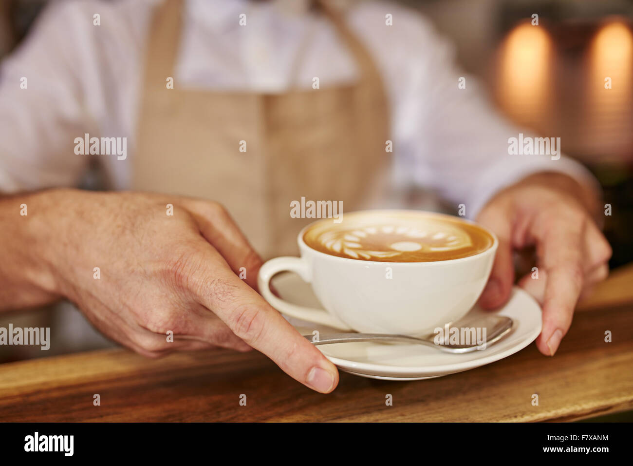 Close up of man serving coffee at cafe. Focus on male hands placing a cup of coffee on wooden counter. - Stock Image