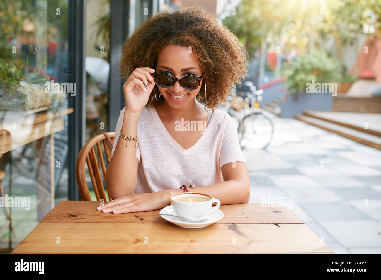 Portrait of pretty young girl at outdoor cafe.  African young woman wearing sunglasses looking at camera. - Stock Image