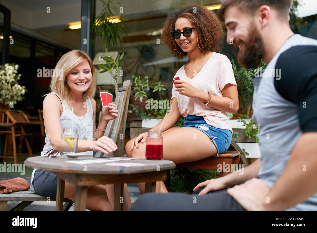 Group of friends playing a game of cards in a cafe. Woman picking up a playing card on table and smiling. - Stock Image
