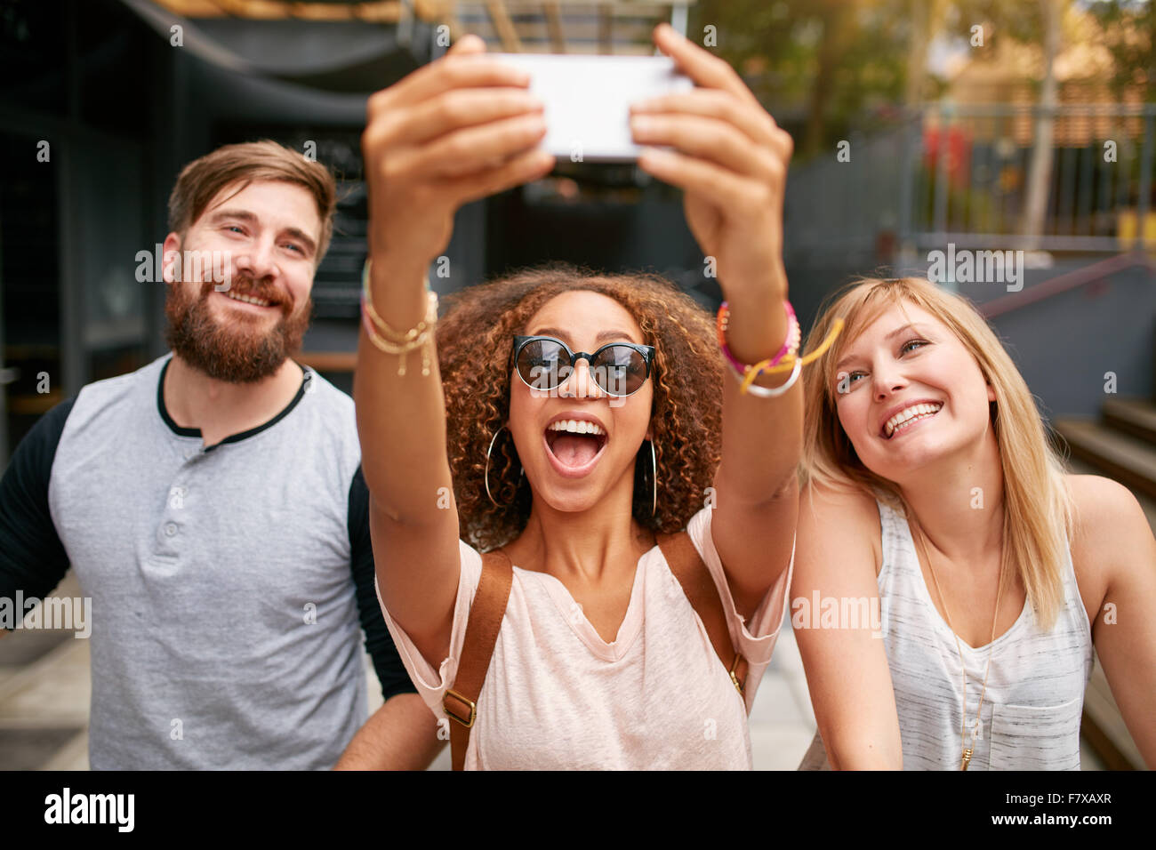 Group of smiling friends taking selfie with mobile phone. Multiracial man and women enjoying themselves outdoors - Stock Image