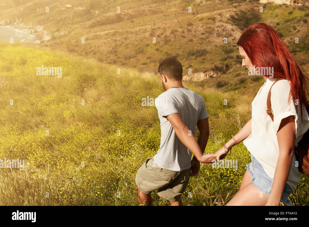 Outdoor shot of young couple enjoying on their vacation, walking down a peak holding hands. Caucasian couple hiking - Stock Image