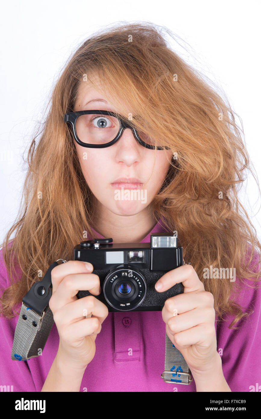 Shocked young photographer with a camera in her hands - Stock Image