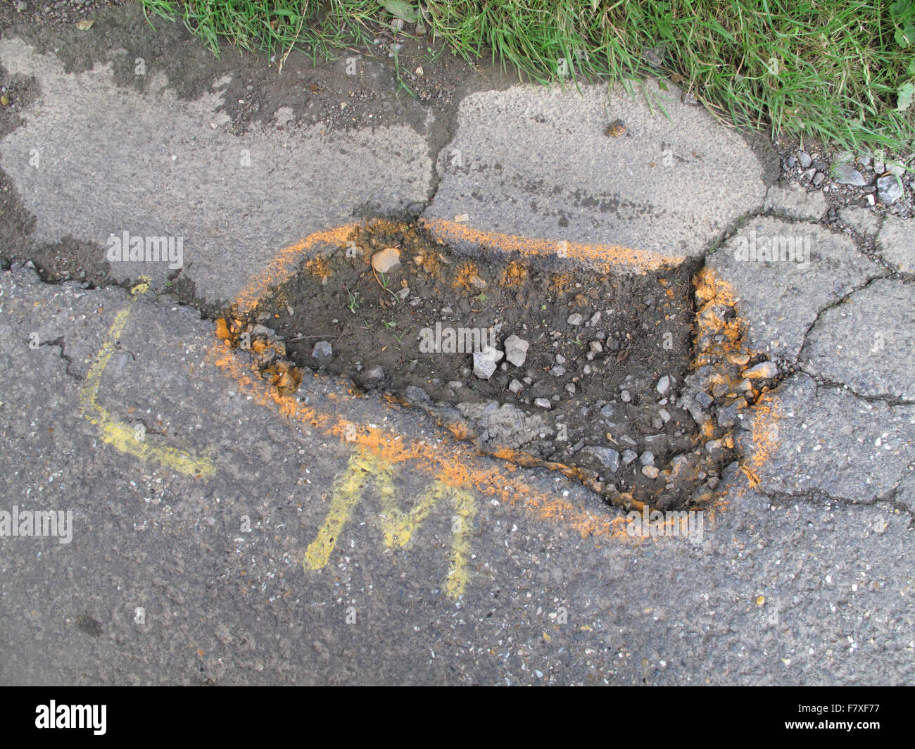 Potholes in broken tarmac country road marked to warn cyclists of danger, Berkshire, England, July - Stock Image