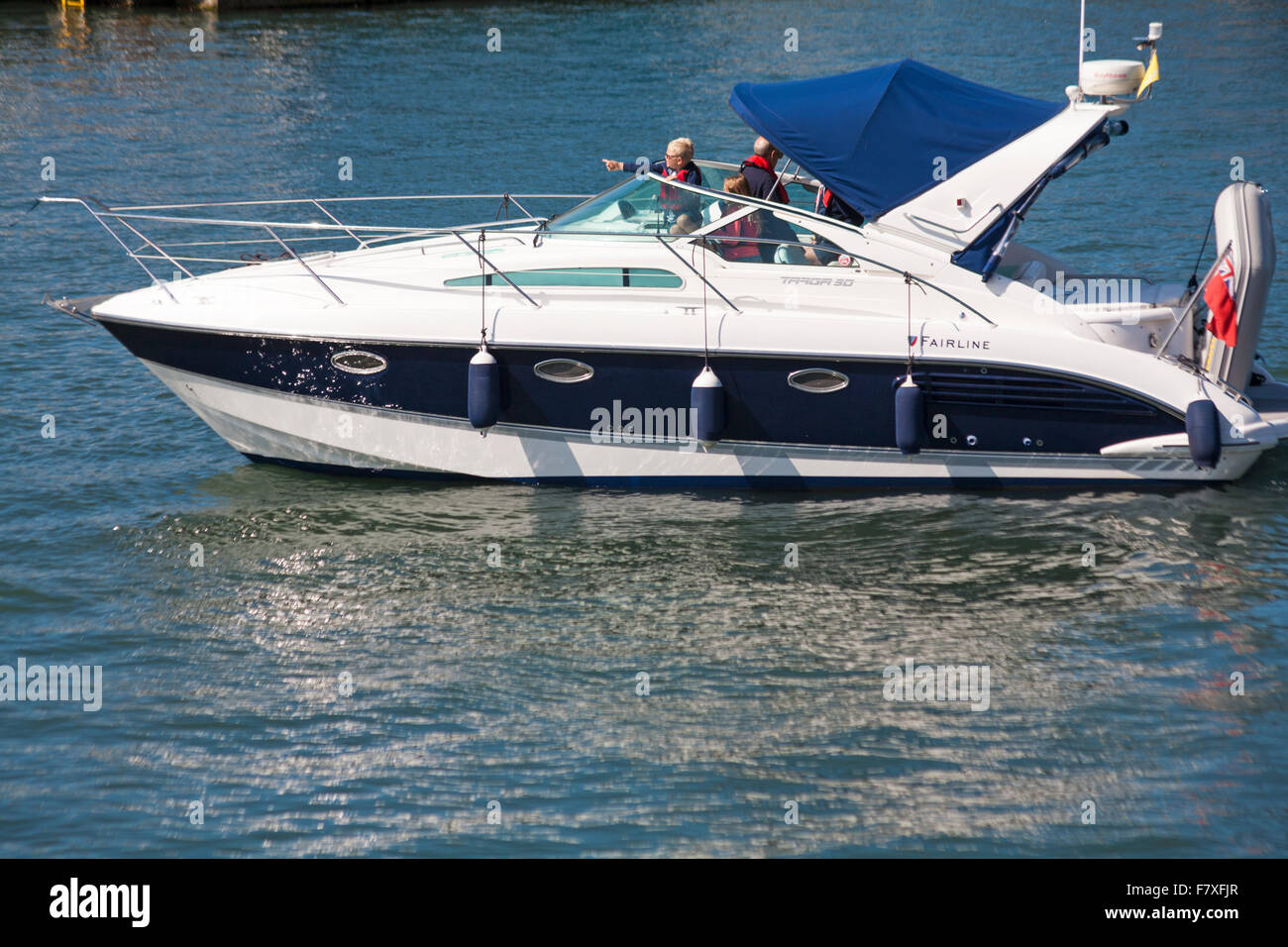 Family enjoying cruising around Poole Harbour in a Fairline Targa 30 speedboat in July - Stock Image
