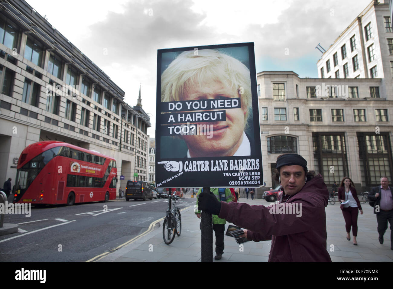 Man holding placard advertising haircuts with reference to Boris Jonson, the London Mayor known for his unruly hair, - Stock Image