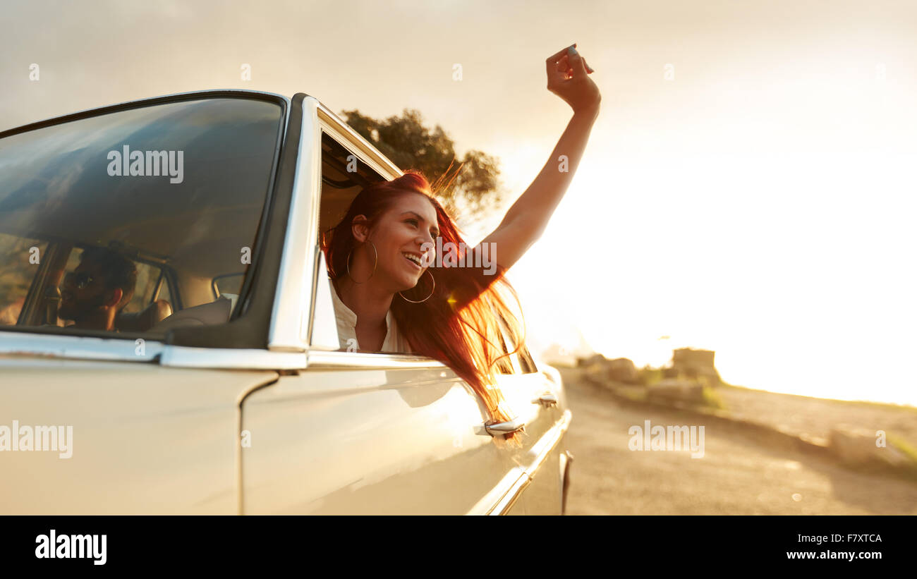 Shot of beautiful young woman enjoying road trip on a summer day. Excited young female raising her hand out of the - Stock Image
