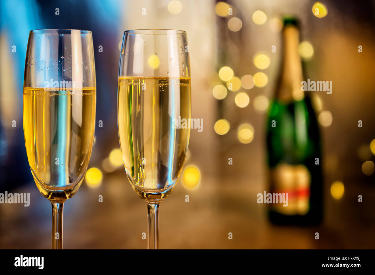 Image of two champagne glasses with bottle and blur lights in background Stock Photo