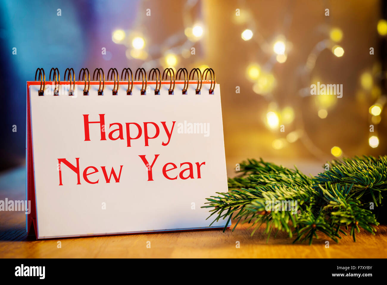 Image of empty ring binder and text Happy New Year, branch and blur lights in background - Stock Image