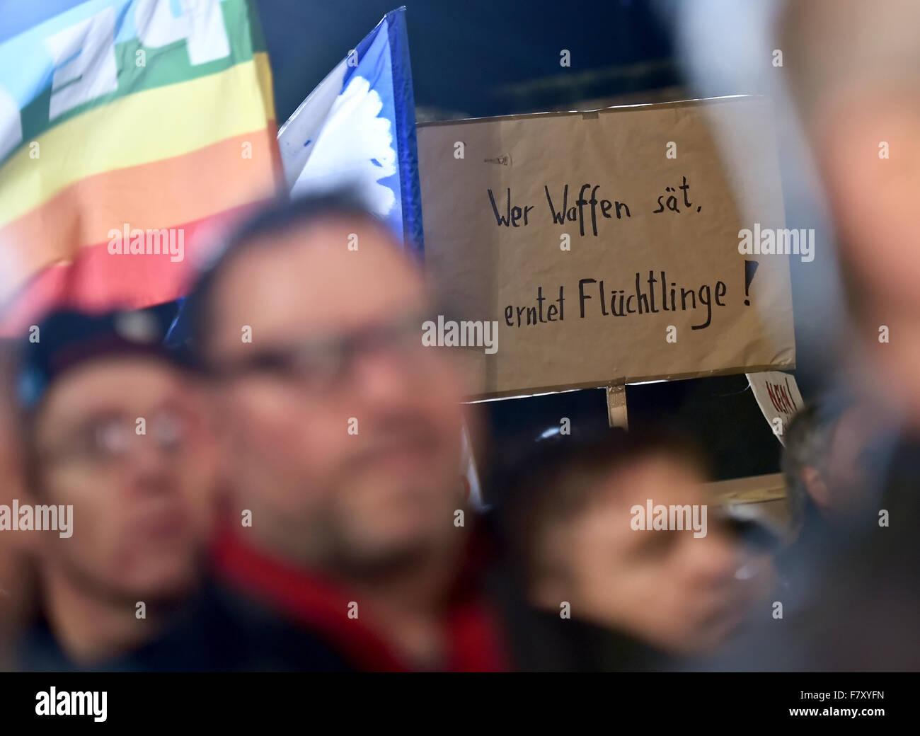 "Berlin, Germany. 3rd Dec, 2015. A demonstrator holds a sign that reads ""Wer Waffen saet, erntet Fluechtlinge!"" (lit. Stock Photo"