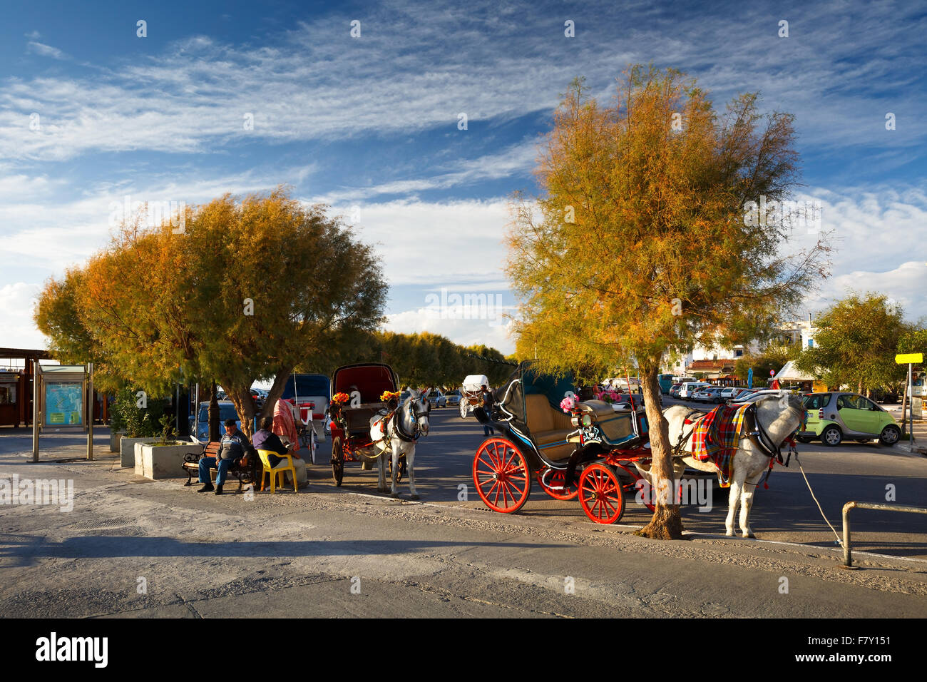 Horses and carriages at the seafront of Aegina town on Aegina island, Greece - Stock Image